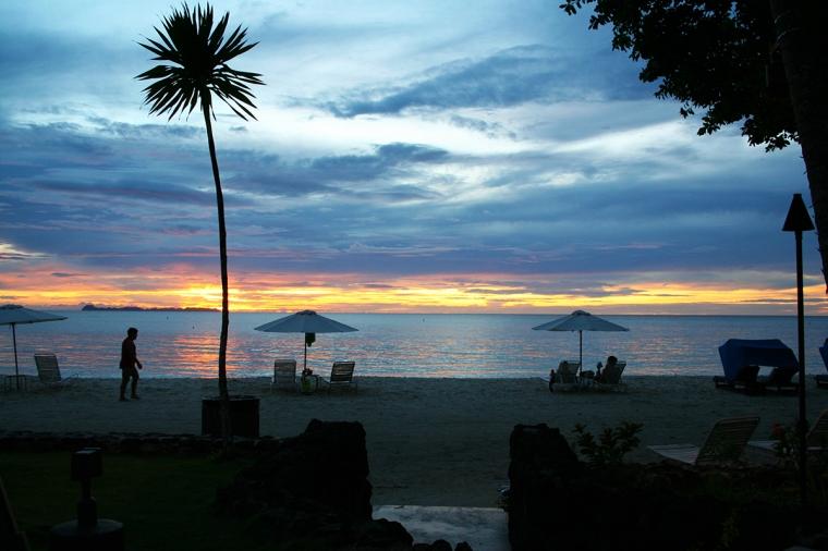 Strand med solnedgång i havet.
