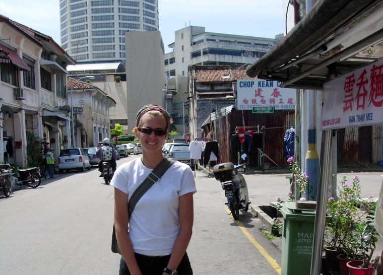 En tjej på en gata med skyltar med kinesiskt tecken.
