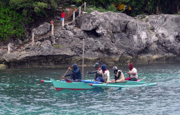 """5 personer med """"rånarluvir"""" paddlar i en kanot."""
