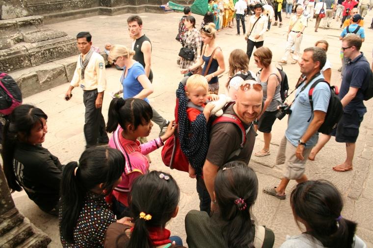 En man med ett barn i bärstol omgiven av nyfikna människor.