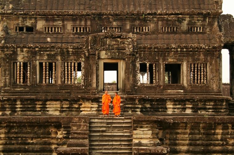 Två munkar i orangea dräkter vid en tempelruin.