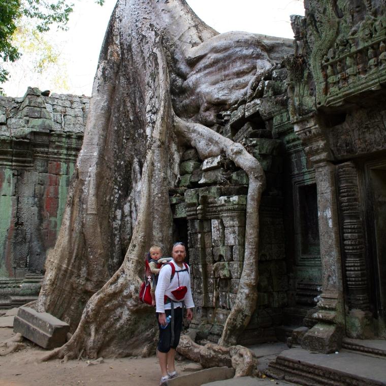 En man med ett barn i en bärstol ståendes framför en tempelruin där ett träd vuxit sig in.