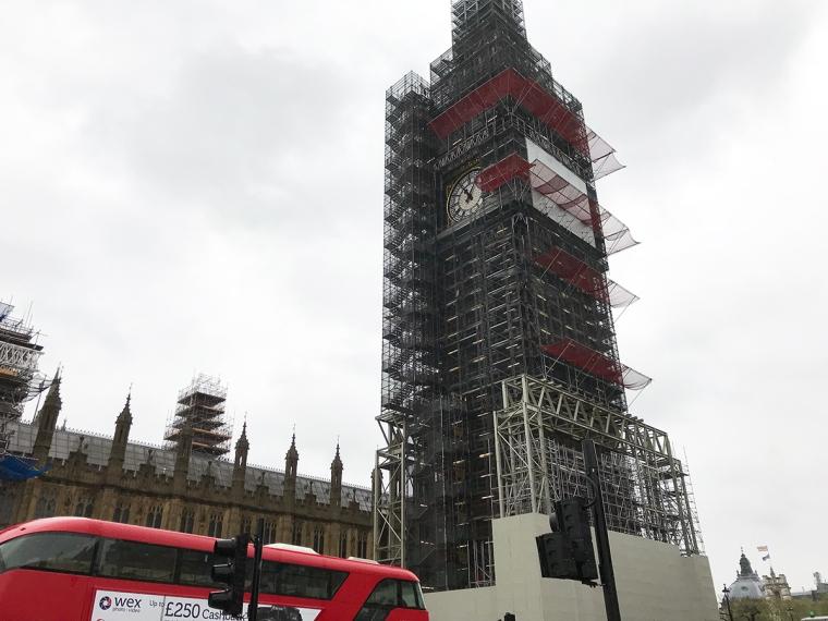 Ett klocktorn omslutet av byggställningar.