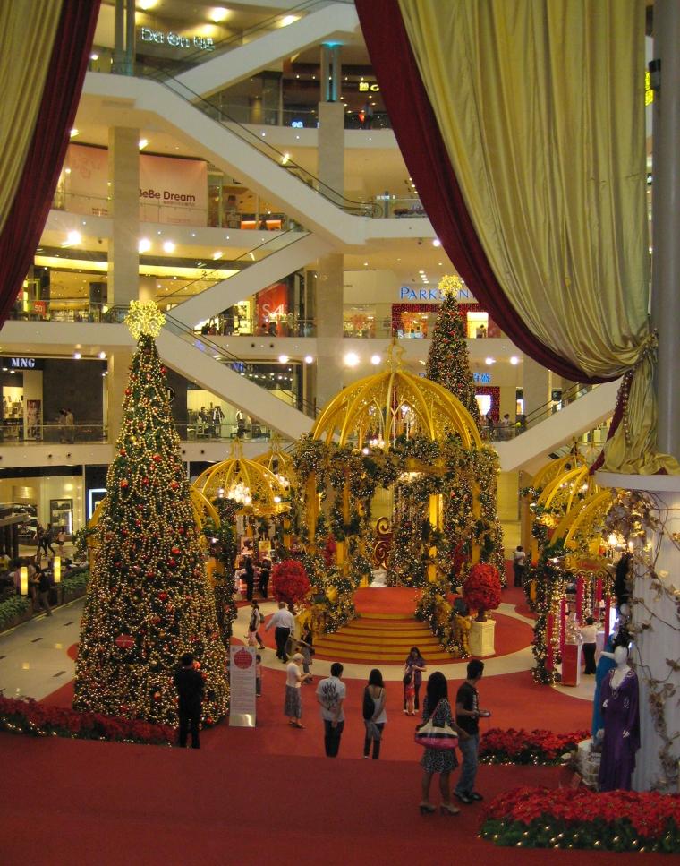 Julgran, belysnbing och glitter i ett köpcentrum.