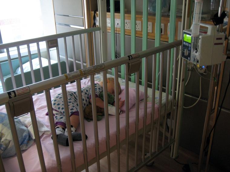 Ett barn ligger med dropp i en säng på ett sjukhus.