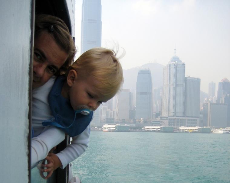 En kvinna och ett barn tittar ut genom ett fönster, storstad i bakgrunden.