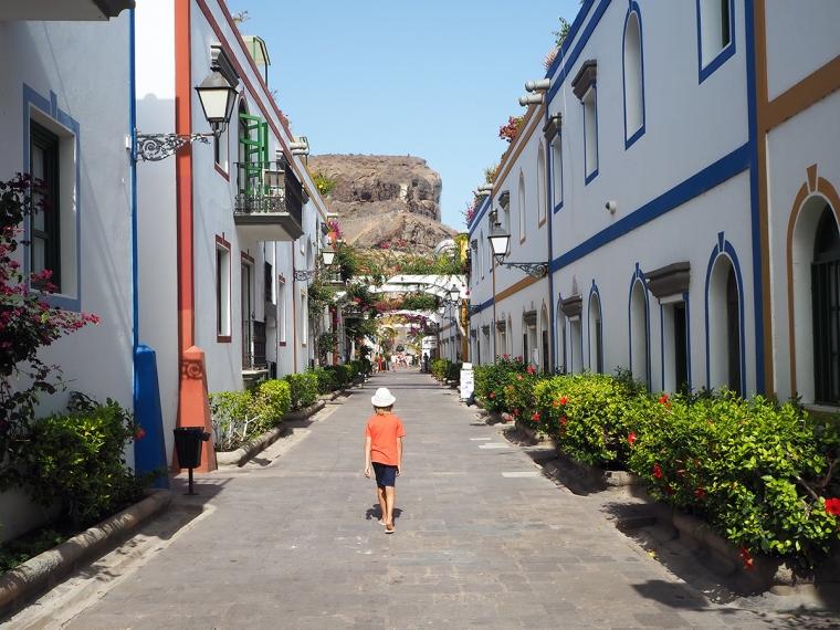En gata med vit hus med färgglada detlajer.