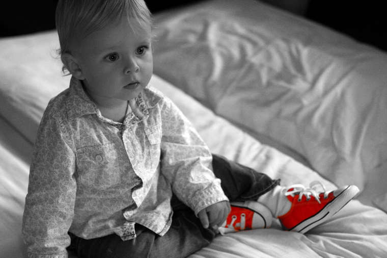 Ett svartvitt bild på ett barn med röda skor.