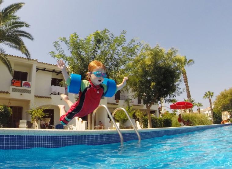 Ett barn med armpuffar kastar sig i poolen.