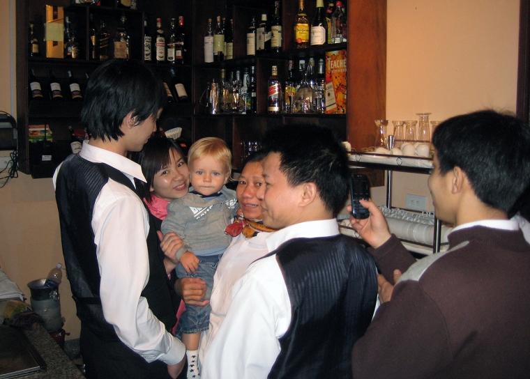 Vietnamesisk personal på en restaurang håller ett svenskt barn i famnen.