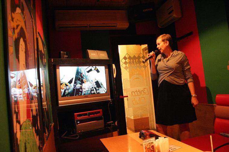 En kvinna står framför en tv och sjunger i en mikrofon.