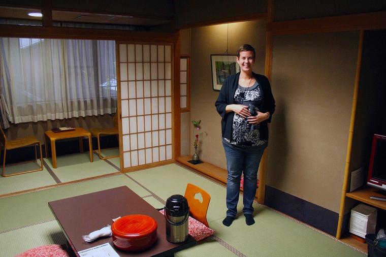 EN gravid kvinna står ett rum med låga möbler på golvet.