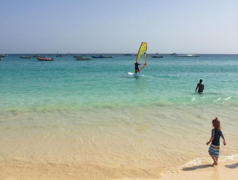 Turkost hav, en vindsurfare och ett barna på stranden.