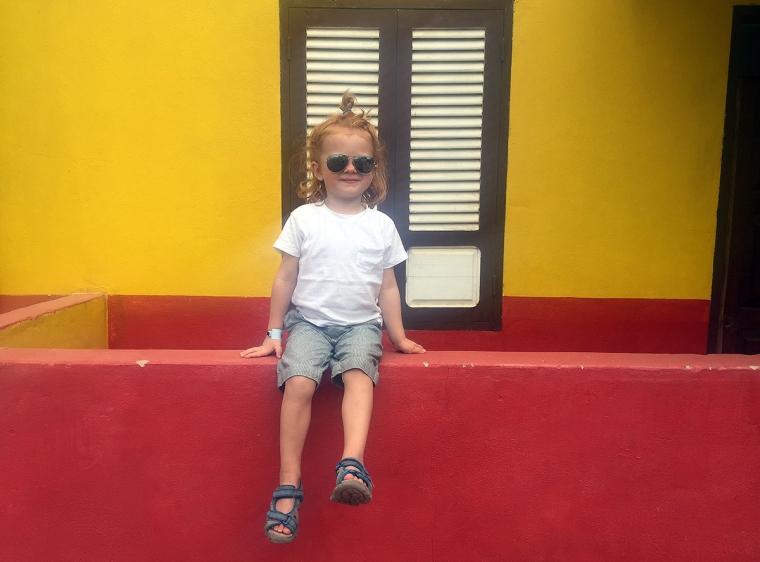 Ett barn i solglasögon sitter på en röd mur.