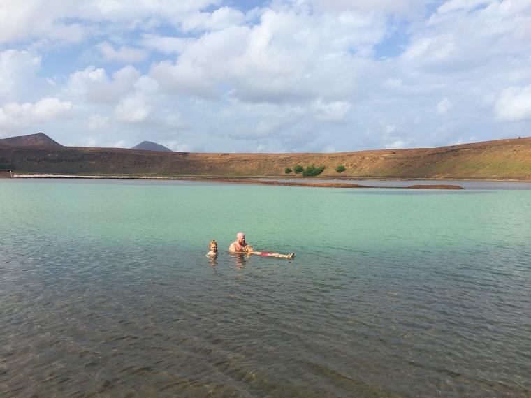 En man och två barn badar i en sjö.