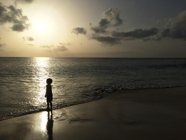 Ett barn på en strand i solnedgång.