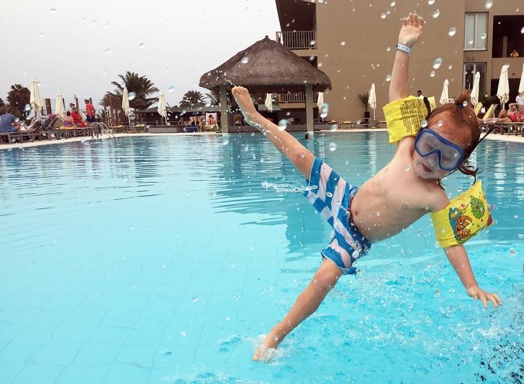 Ett barn hoppar i poolen.