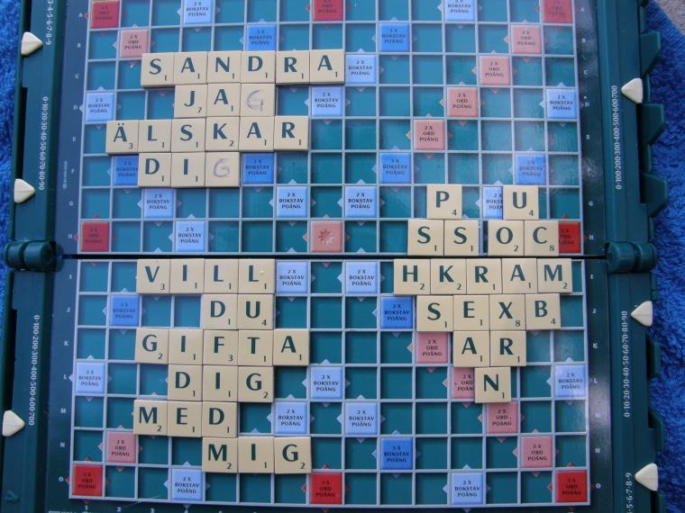 Ett alfapetspel där brickorna bildar ordet: Sandra jag älskar dig. Vill du gifta dig med mig? Puss och kram sex barn.