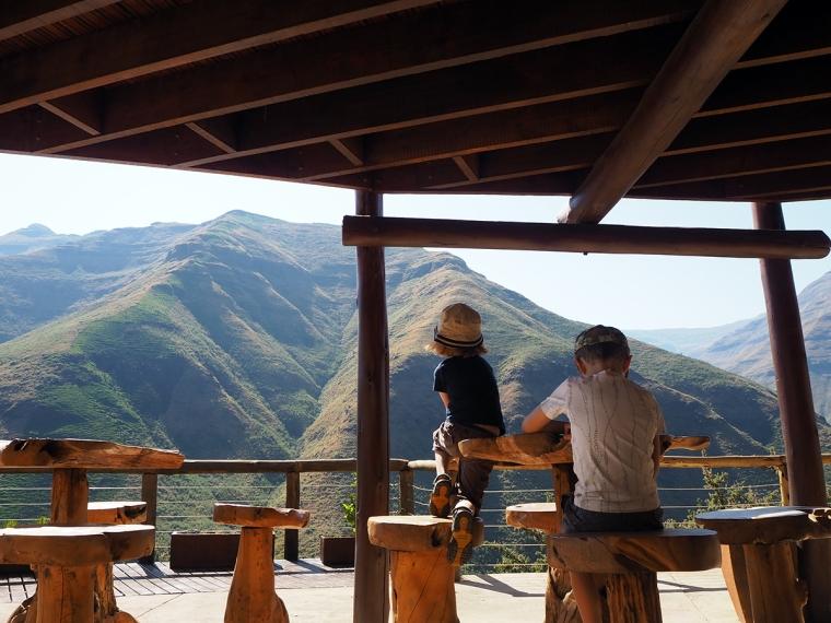 Två barn bakifrån och utsikt över berg.