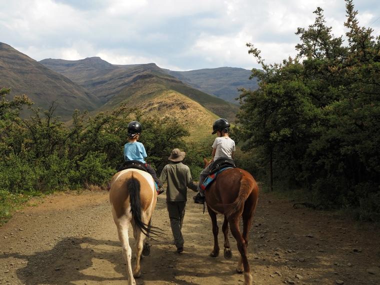 Två barn p var sin häst.