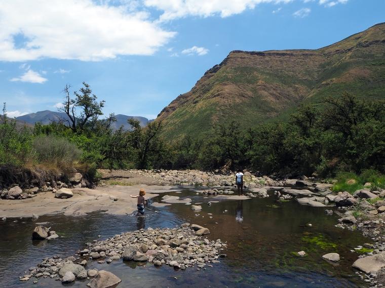 Två barn leker i vatten. Berg i bakgrunden.