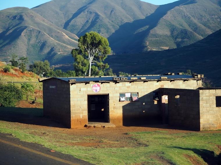 Ett litet tegelhus med verg i bakgrunden.