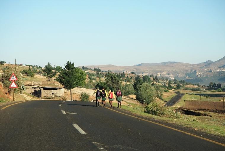 Barn med ryggsäckar går längs en väg.