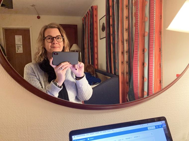 En en kvinna som tar kort på sig själv i en spegel med lekande barn i bakgrunden.