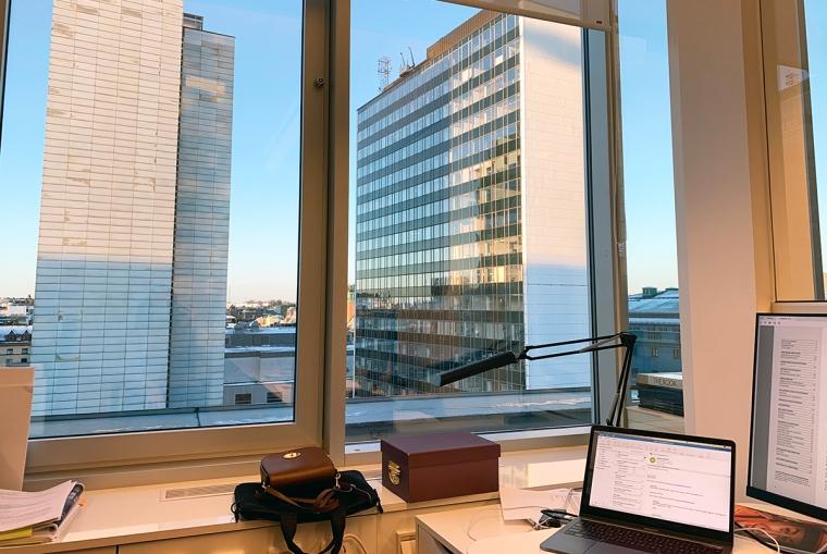 En kontorsplats med stort fönster och utsikt över Hötorgsskraporn.