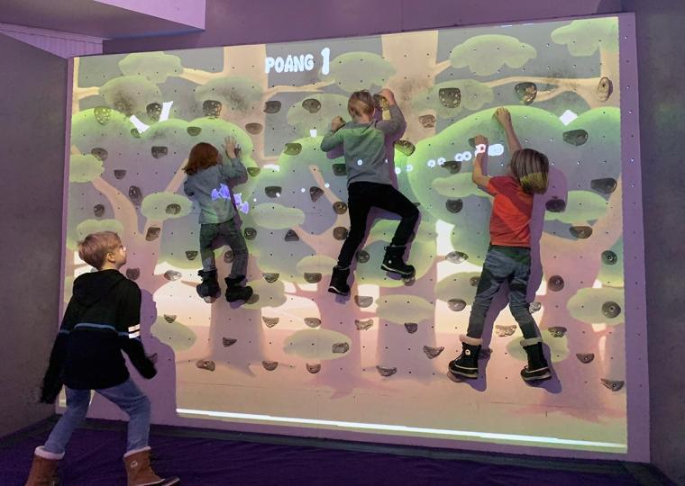 Fyraw barn som klättrar på en klättervägg.