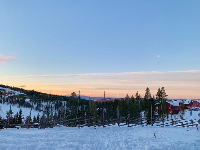 Snölandskap med bergstoppar i bakgrunden.
