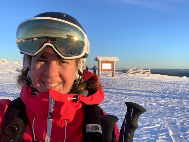 En skidåkare på toppen av ett berg i eftermiddagssol.
