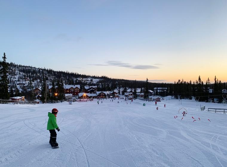 Ett barn på snowboard.