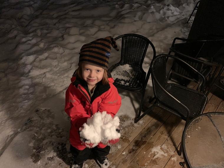 Ett barn som står ute och håller fram händerna med snö.