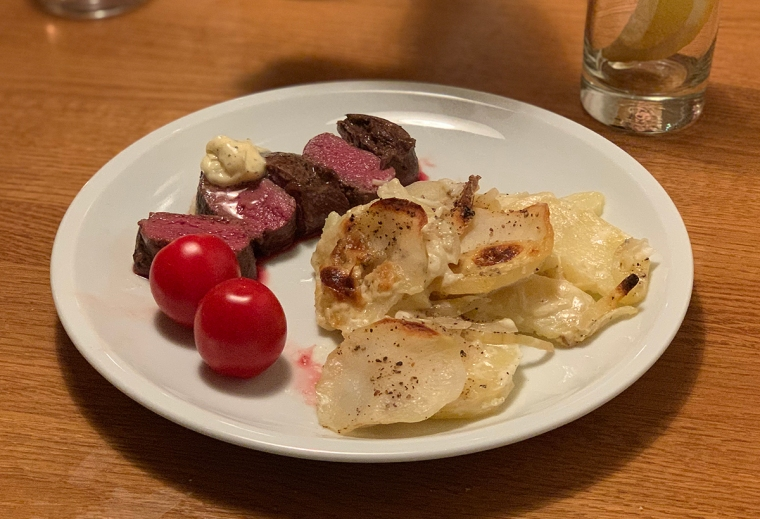 En tallrik med renkött, tomater och potatisgratäng.