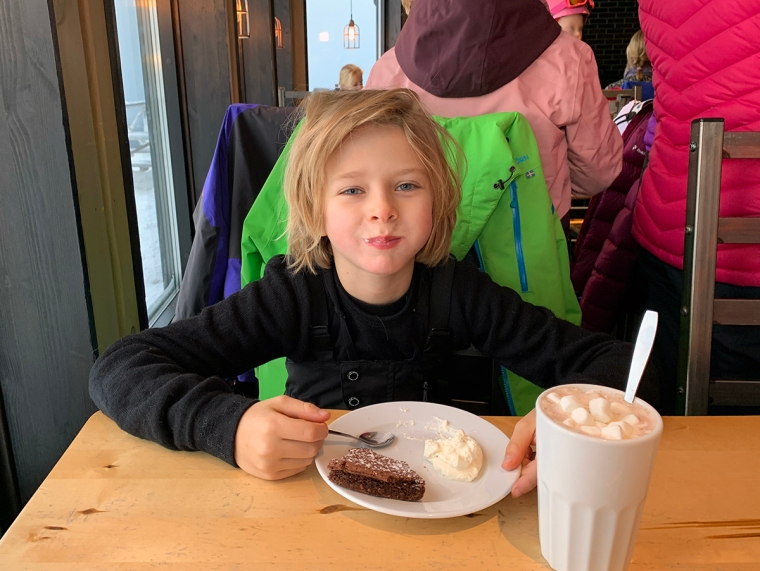 Ett barn som äter kladdkaka och dricker varm choklad.