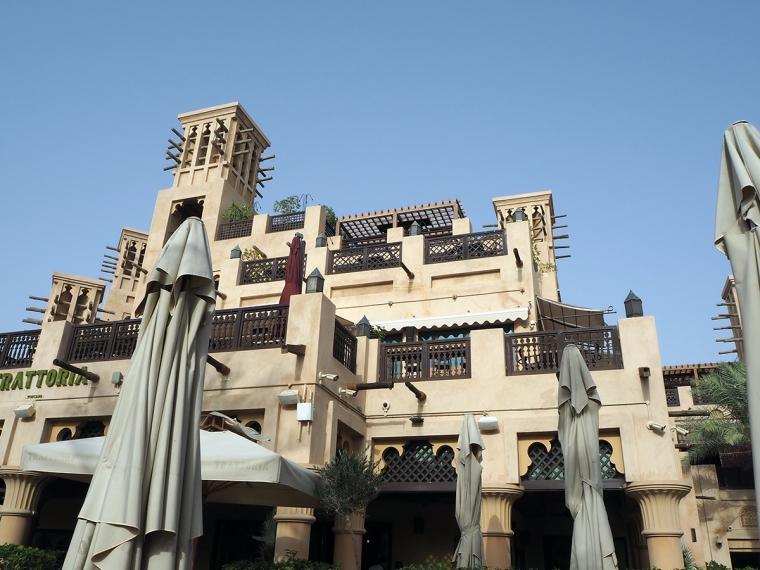 Ett ljusbrunthus med flera balkonger och terrasser.