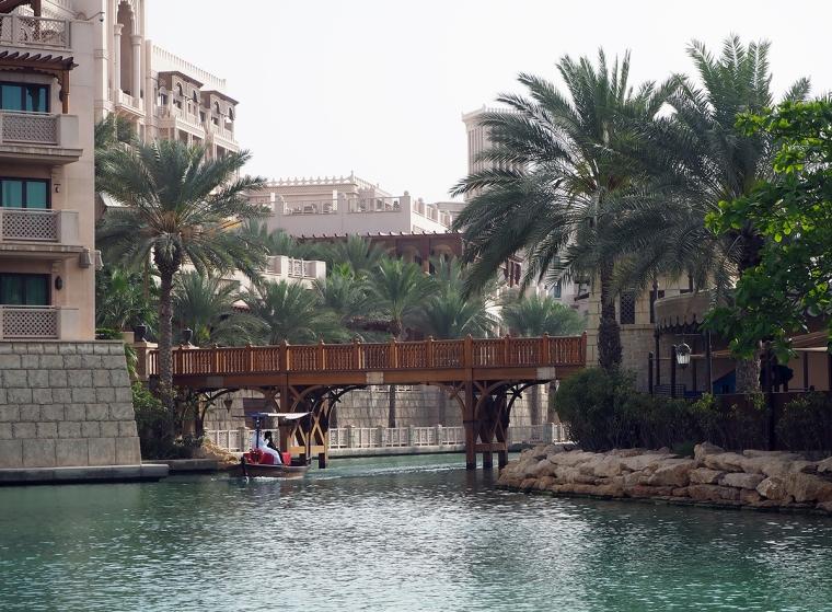 En kanal med en bro över och en båt som glider under.