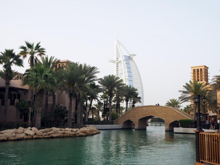En kanal med en bro och en stor byggnad i bakgrunden som ser ut som ett segel.