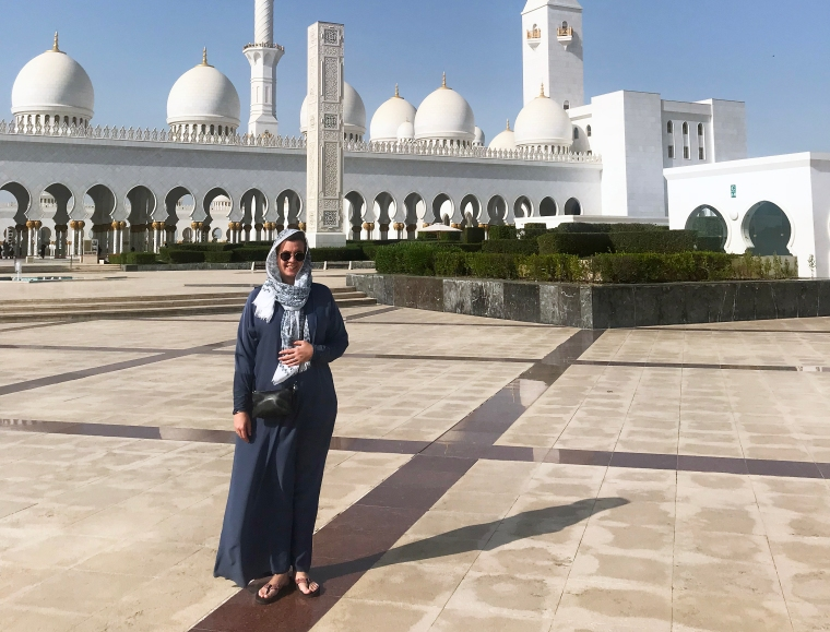 En kvinna i blå hellång dräkt med en sjal runt huvudet framför en vit moské.