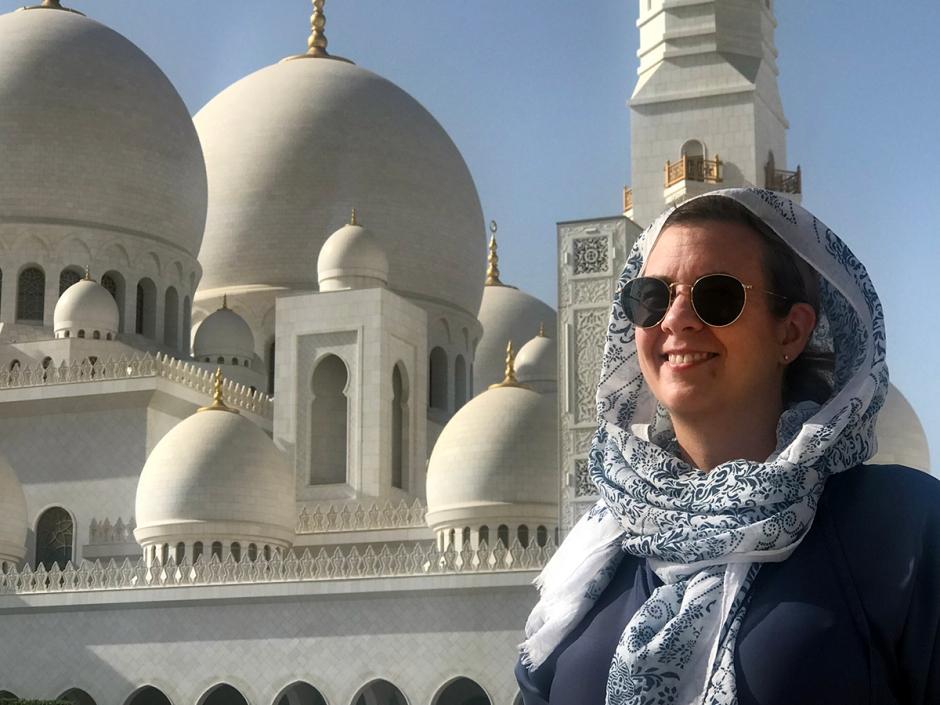 En kvinna med huvudsjal framför en vit moské.