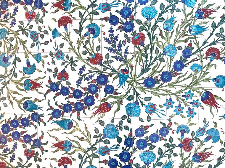 Vita kakelplattor med blå och röda blommönster.