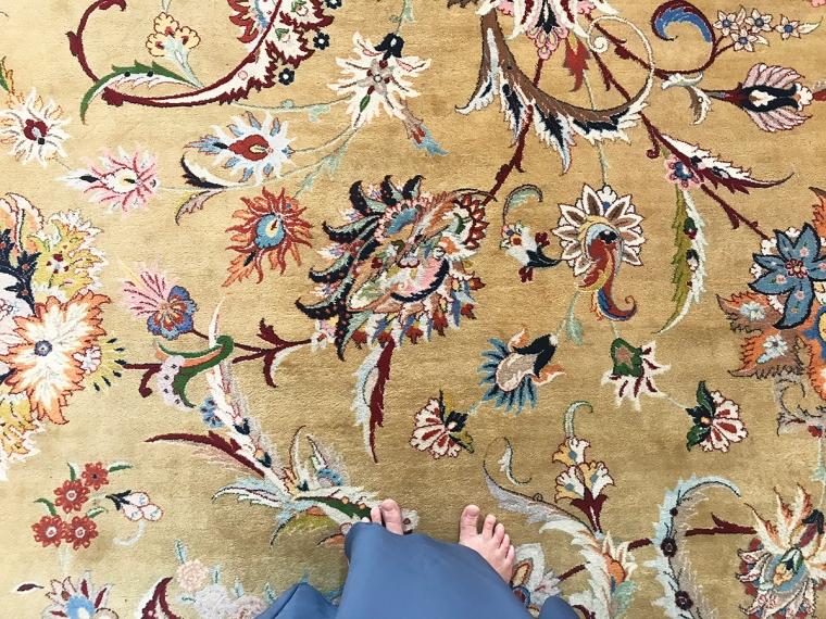 En beige matta med blommönster.