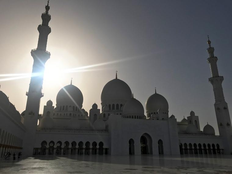 En vit moskébyggnad i motljus.