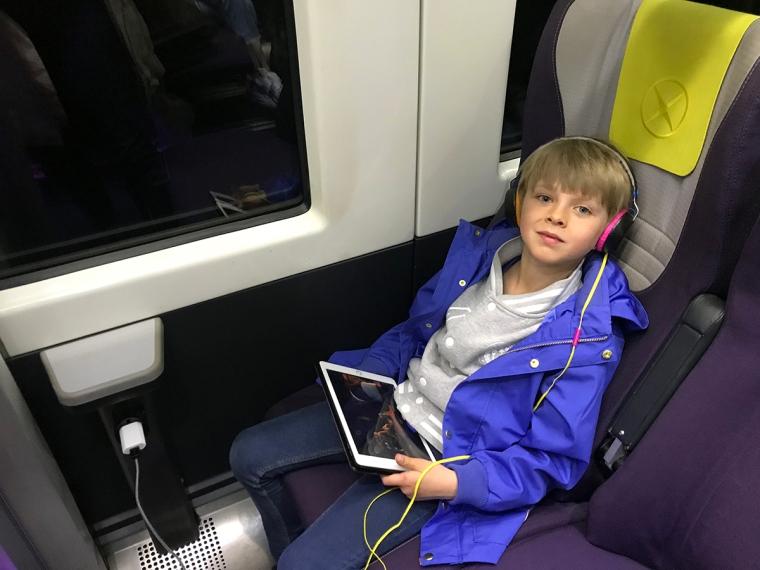 Ett barn sitter med en iPad och hörlurar på ett tåg.