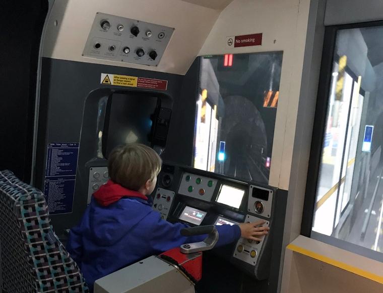 Ett barn kör tunnelbana i en simulator.