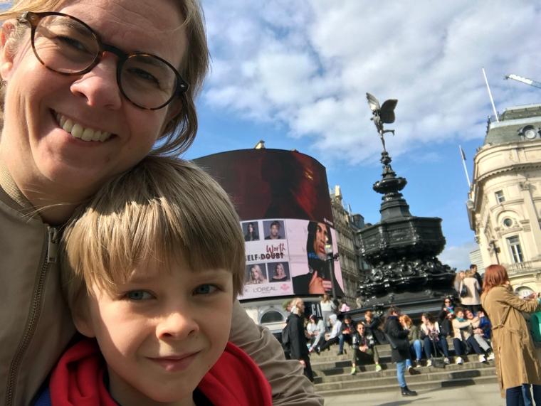 En kvinna och ett barn tar en selfie framför fontänen på Piccadilly Circus.