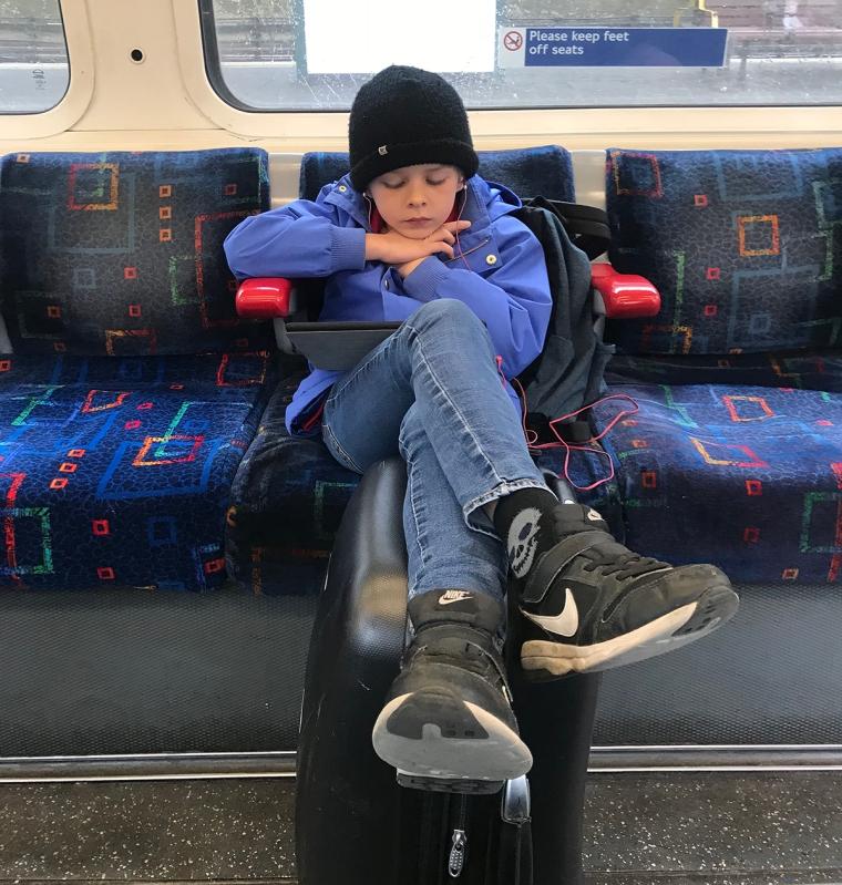 Ett barn sitter på tunnelbanan och tittar på en iPad.