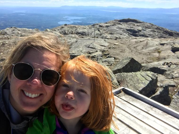 En kvinna och ett barn tar en selfie med berg i bakgrunden.