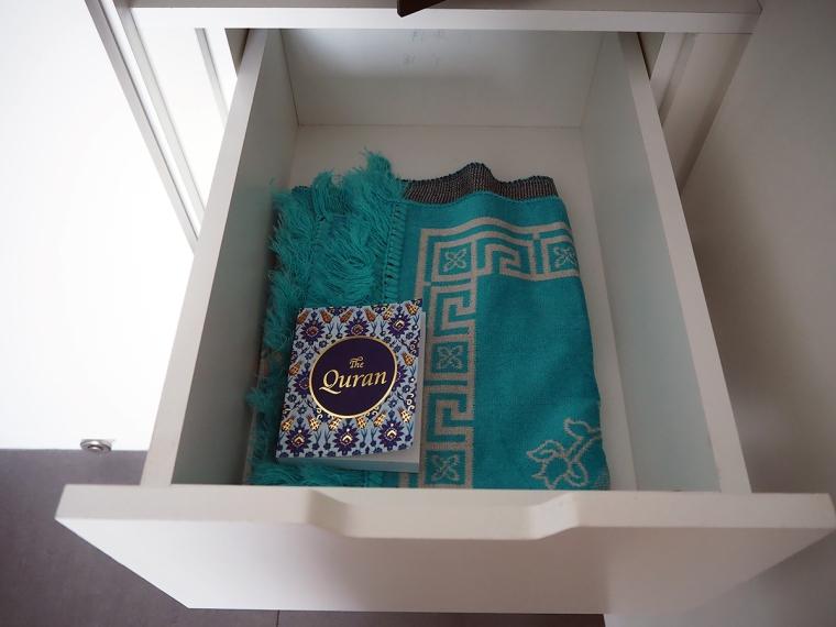 En utdragen låga med en bönematta och en koran.